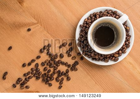 Coffee cup and coffee beans on wooden background. Top view.
