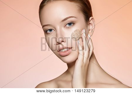 Beauty portrait of an attractive girl who smears on the face scrub.