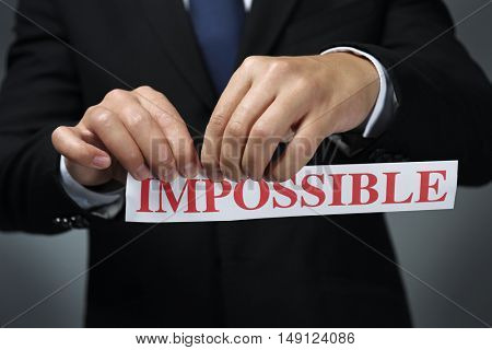 Businessman tearing paper with impossible word
