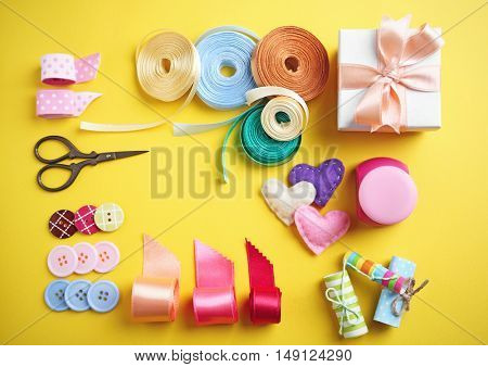 Tailor set of ribbons and scissors on yellow background