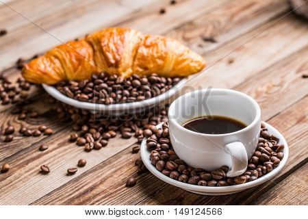 Breakfast coffee - cup, sugar, milk jug and croissant with coffee beans on wooden background.
