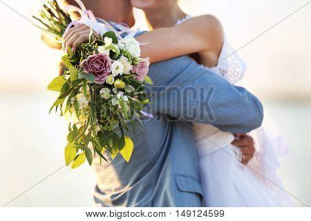Groom and bride hugging, outdoor