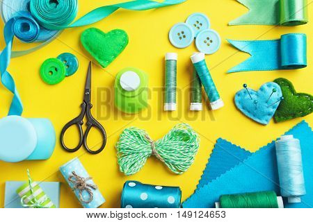 Tailor set of ribbons, threads and scissors on yellow background