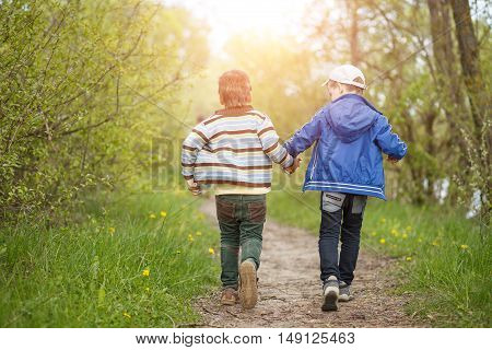 Boys friendship background. Two small funny boys running away on trail in countryside