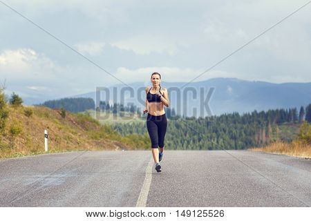 Young Female Runner On Road Cross In Mountains.