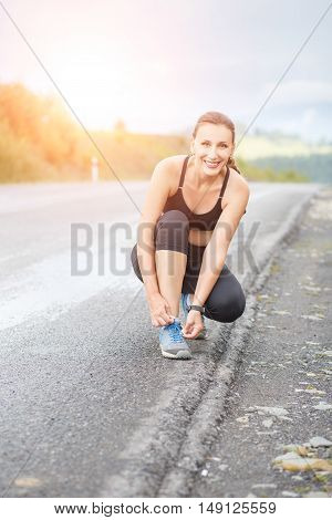Young Fitness Woman Tying Her Shoes Before Jogging