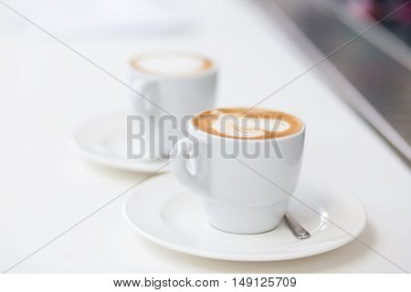 Two Cups Of Cappuccino On Counter In Cafe