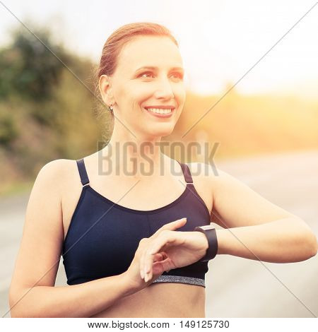 Young Smiling Fitness Woman Using Her Smart Watch