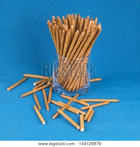 Long sticks are in a glass on a blue background. Placer salty sticks.