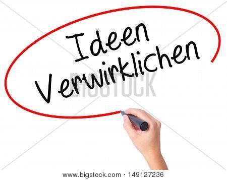 Women Hand Writing Ideen Verwirklichen ( Realize Ideas In German) With Black Marker On Visual Screen