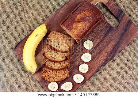 Homemade banana cake with sliced banana and whole banana on butcher served.