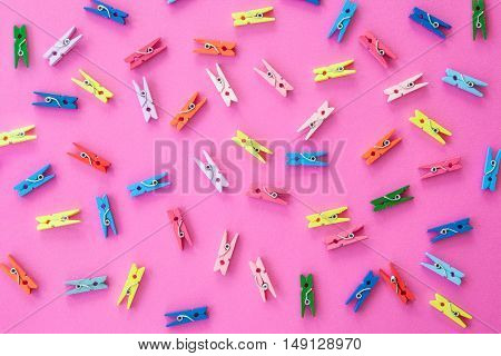 Little colorful clothes pins on a pink background