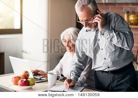 Teamwork. Man talking on the phone and taking notes while lady typing something on her laptop and smiling
