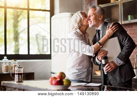 Happy kissing good-bye. Grey-haired elegant couple kissing before husband getting to his job