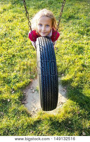 Young girl in autumn park having fun on tire swing.
