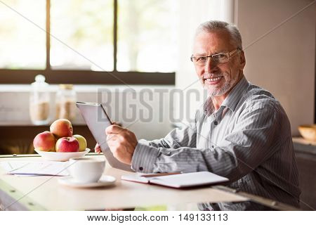 Enjoyable breakfast. Good-looking old man in glasses working on laptop while having morning coffee