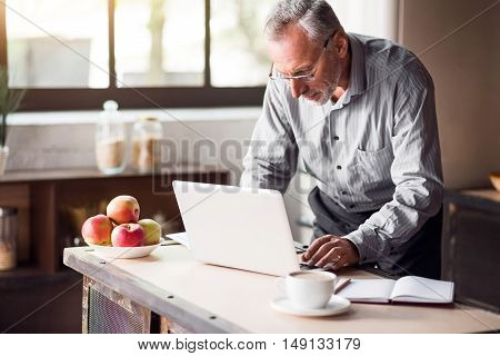 Busy morning. Middle-aged businessman using computer in the kitchen of his cosy house