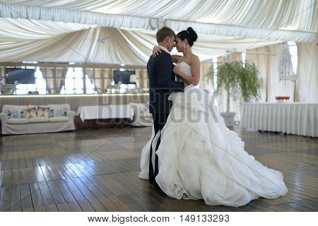 Wedding couple in the restaurant is dancing. Beautiful model girl in white dress. Handsome man in suit. Beauty bride with groom. Female and male portrait. Woman with lace veil. Lady and guy indoors