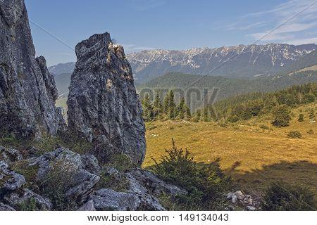 Scenic alpine view with vertical rock vast valley and Piatra Craiului mountain range in Magura Transylvania region Romania. Romanian travel destinations.