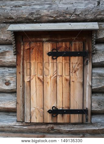 Window with wooden shutters with artistic forging. Traditional architecture of the Russian countryside. Russia.