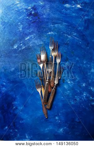 Cutlery, Spoons And Forks. Bright Blue Background.