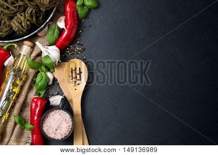 Vegetables fresh herbs hot spices and household goods stacked on a stone countertop. Photo includes a copyspace