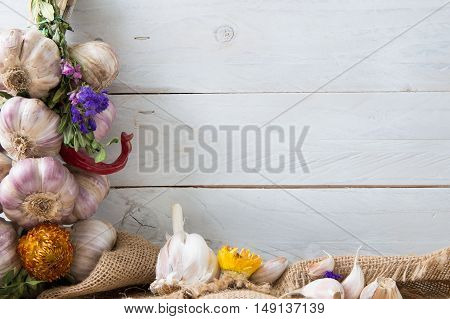 Composition of fresh garlic dried herbs and flowers. Photo includes a copyspace