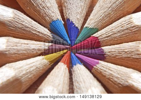 Many different colored pencils on wooden background