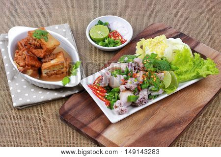 Gold bar soup as fried tofu wrap minced pork in soup served with spicy and sour mixed herb salad with squid wrap minced pork  are Thai cuisine and  sliced lemon grass,kaffir lime leaves,minced red chili,and lettuce.