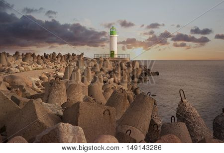 Sunset view of lighthouse sea and concrete breakwater in Ventspils Latvia