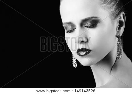 Portrait of beautiful young woman with earrings. Black and white