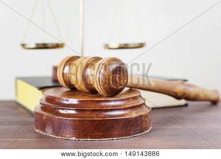 Symbols of law: wood gavel soundblock scales and volumetric book on a wooden table