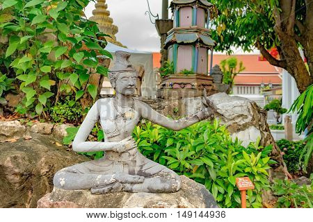 Detailed Hermit statue and architecture in Wat Pho, Buddhist temple, Bangkok, Thailand. Wat Pho known also as the Temple of the Reclining Buddha.