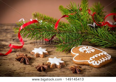 Old wooden christmas background with gingerbread cookies and fir branch