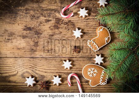 Old wooden christmas background with gingerbread cookies, sweets and fir branch, empty space for text