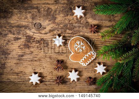 Old wooden christmas background with gingerbread cookies and fir branch, empty space for text