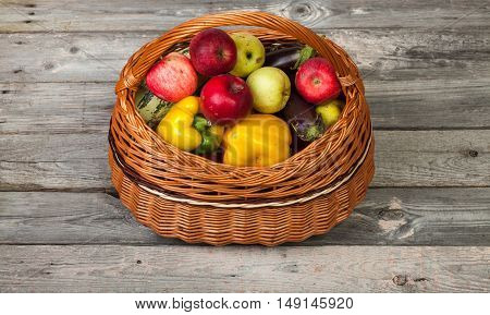 Colorful vegetables and apples in basket on old wood table