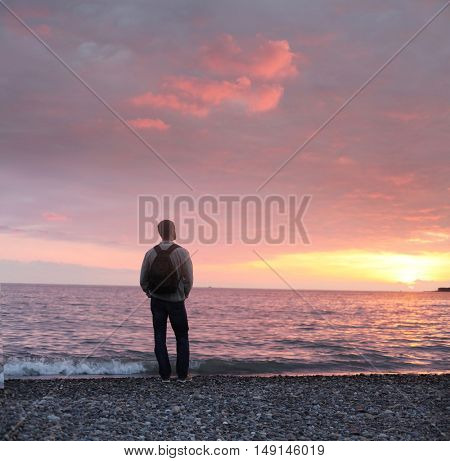 alone man looking at the sunset on a beach