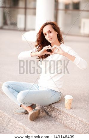 Smiling girl 20-24 year old showing heart with hands. Drinking coffee outdoors. Looking at camera.