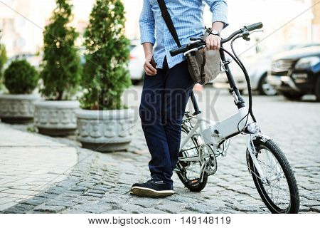 Rest after ride. Handsome man riding on bike and holding cellphone while standing on the street.