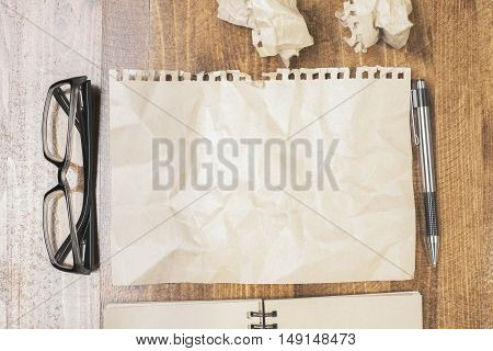 Top view of wooden desktop with crumpled brown paper sheet pen spiral notepad and glasses. Mock up