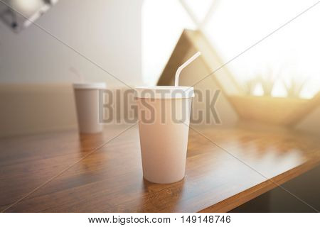 Closeup of empty coffee cup with straw placed on wooden table. 3D Rendering