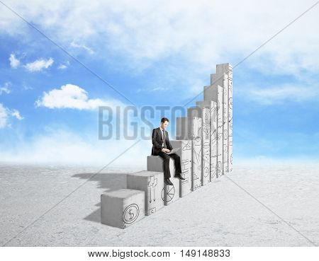 Young businessman using laptop computer while sitting on abstract concrete chart bars with business doodles on sky background. Success concept
