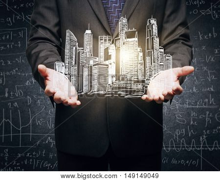 Closeup of businessman's hands holding abstract illuminated city sketch on concrete background with mathematical formulas
