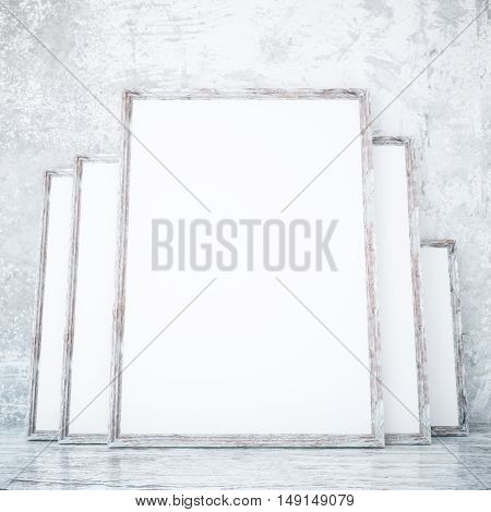 Room with several empty picture frames leaning on textured concrete wall. Mock up 3D Rendering