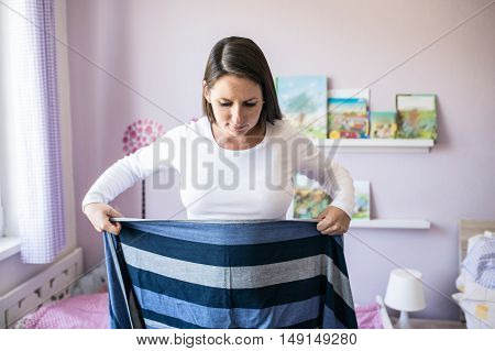 Beautiful young mother wrapping sling for baby around her in her bedroom