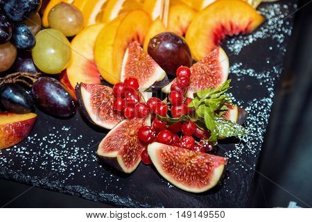 Closeup sliced fruits and berries arrangement on a black stone tray -  fig and viburnum cluster, peach, orange and grape, decorated by mint and sugar powder