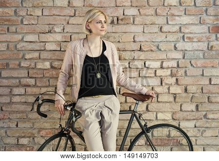 Stylish young woman leaning against bicycle front of brick wall.