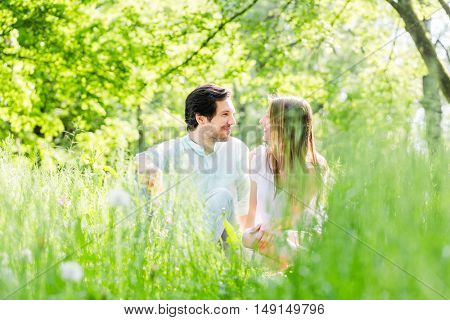Couple in grass on meadow looking at each other