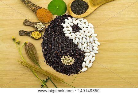 Black rice and white pill forming a yin yang symbol and  turmeric powder , millet , soybean , basil seed in wooden spoon on brown wooden blending of herb and medicine